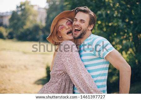 Young woman and young man are hugging and smiling
