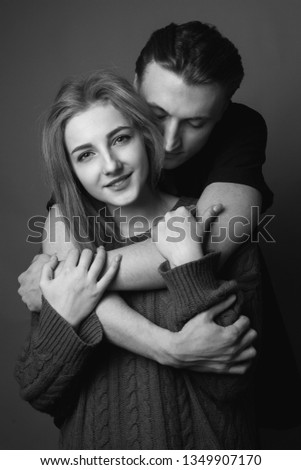 Young woman and young man are hugging and smiling. Black and white