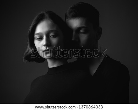 Young woman and young man in studio. Black and white