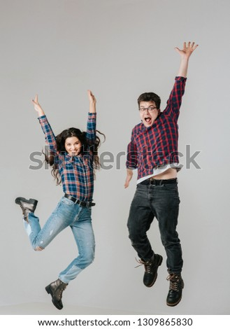 young woman and young man, jumping up, happy,  isolated background gray, studio, close up, positive emotion facial expression