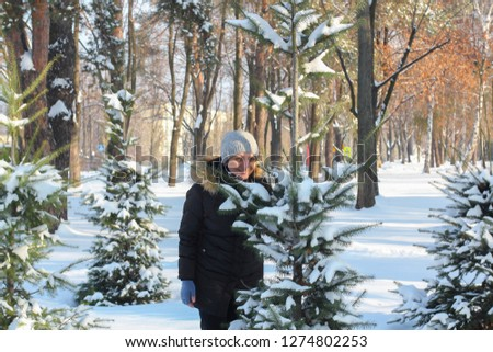 young woman and young man playing snowballs in snowdrift between trees covered in snow