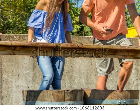 Young woman and young man stomping grapes in wooden barrels during the  Grape Stomp Festival; Missouri, Midwest