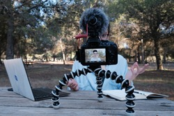 Young woman and youtuber records a video in nature. She's using her laptop to read her video script and her image is featured on her camera' screen.