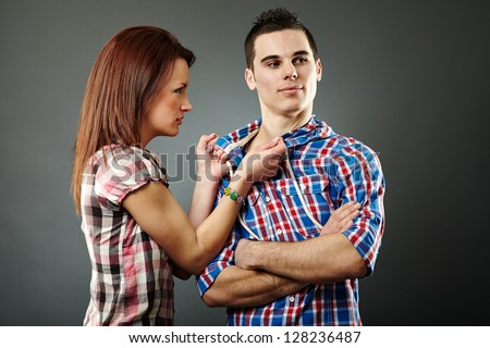 Young woman angry with her indifferent husband. Gray background