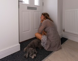 young woman anxiously waiting for mail to arrive through the letterbox