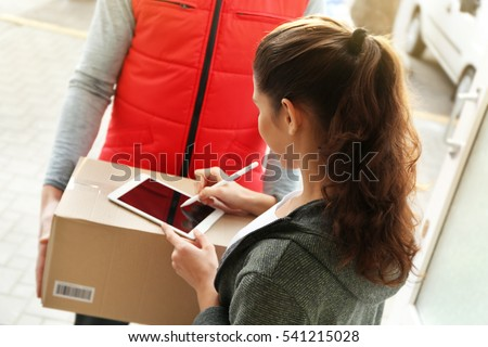 Young woman appending signature after receiving parcel from courier, closeup