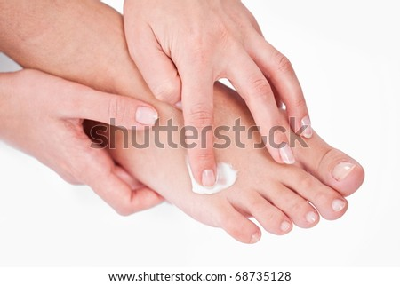 young woman applies cream on her foots. On a white background.
