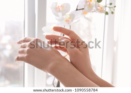 Young woman applying cream onto hands against window