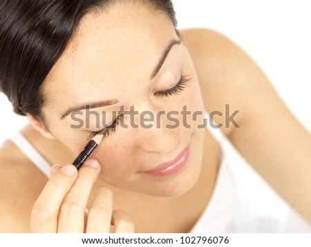 Young Woman Applying Eyeliner. Model Released