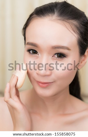 Young Woman applying foundation on face with Powder puff,model is a asian beauty