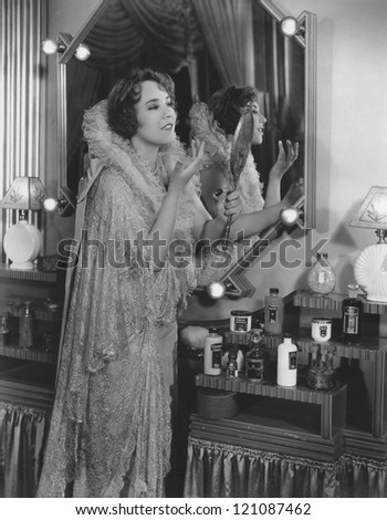 Young woman applying lip balm by dressing table - stock photo