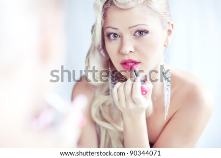 Young woman applying lipstick looking at mirror