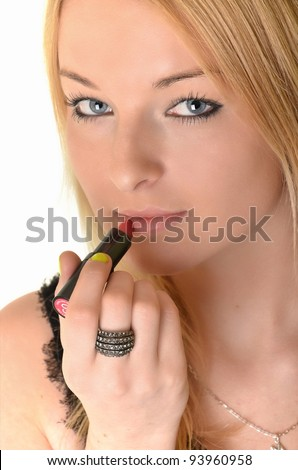 Young woman applying lipstick on white