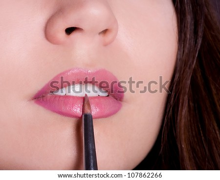Young woman applying lipstick. Professional Make-up