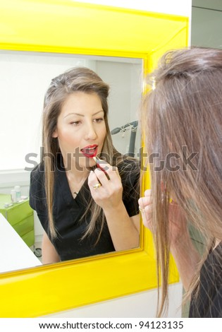 Young woman applying make up in mirror