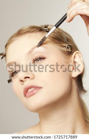Young woman applying make up to eyebrow