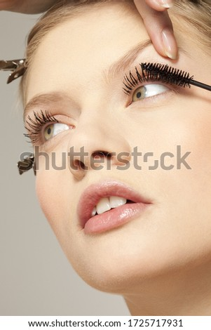 Young woman applying make up to eyelashes