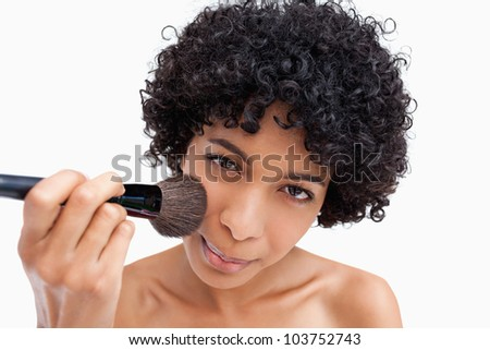Young woman applying natural blush on her face with her powder brush