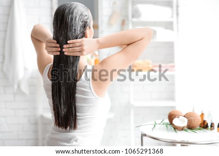 Young woman applying oil onto hair in bathroom #1065291368