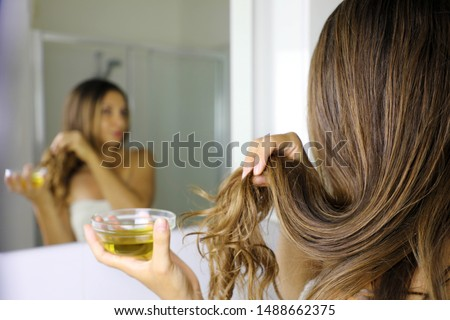 Young woman applying olive oil mask to hair tips in front of a mirror. Haircare concept. Focus on hair.
