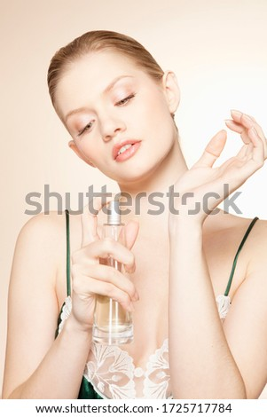 Young woman applying perfume, studio shot
