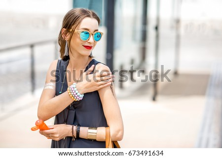 Young woman applying sunscreen lotion standing outdoors at the urban location during the sunny weather #673491634