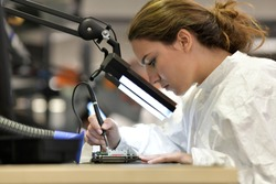 Young woman apprentice working in microelectronics lab