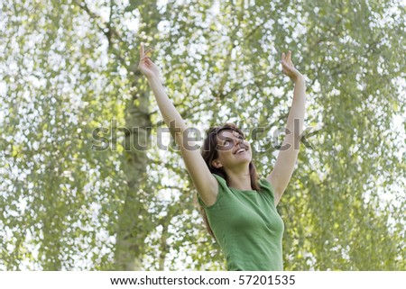 Young woman arms raised enjoying the nature