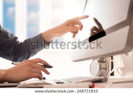 young woman artist in jeans jacket drawing something on graphic tablet and touchscreen at the office