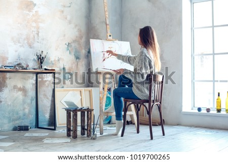Young woman artist painting at home creative painting back view