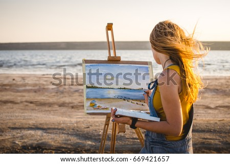 Shutterstock Young woman artist painting landscape in the open air on the beach