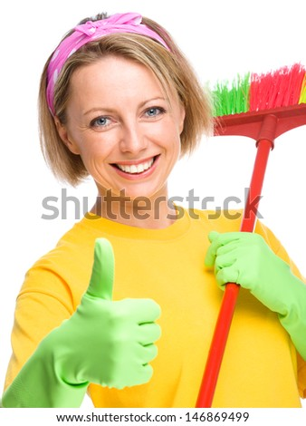 Young woman as a cleaning maid holding broom and showing thumb up gesture, isolated over white
