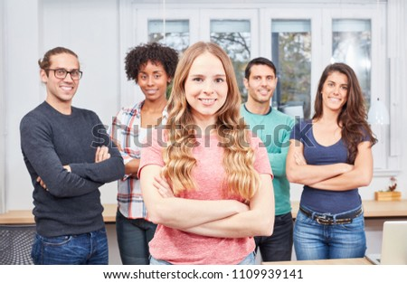 Young woman as apprentice or trainee in internship in front of her business team in the office