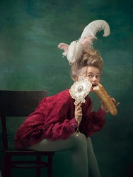 Young woman as Marie Antoinette isolated on dark green background. Retro style, comparison of eras concept. Beautiful female model like classic historical character, old-fashioned.