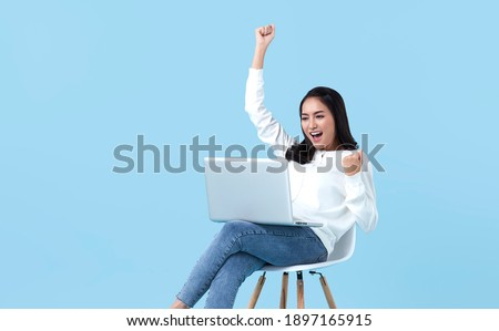 Young woman asian happy smiling celebrate. While her using laptop sitting on white chair isolate on bright blue background.