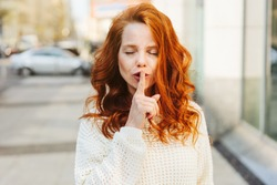 Young woman asking for silence or secrecy standing in a city street with closed eyes and her finger to her lips in a shushing gesture