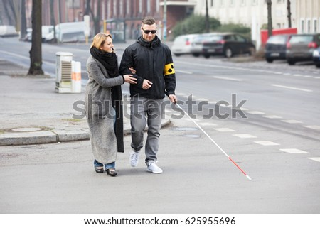 Young Woman Assisting Blind Man With White Stick On Street #625955696