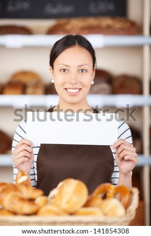 young woman at bakery counter displaying blank paper
