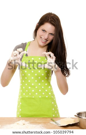 young woman at baking forming claws with her messy dough covered hands on white background