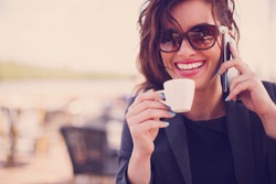 Young woman at cafe drinking coffee and talking on the mobile phone