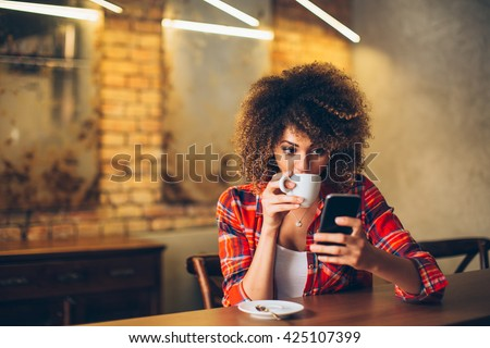 Young woman at cafe drinking coffee and using mobile phone  #425107399