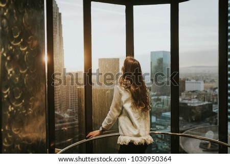 Young woman at elevator window, enjoying the city skyline from the 35 floor, at sunset, with stunning panoramic view of Los Angeles. #1030950364