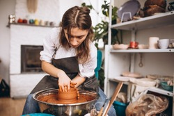 Young woman at her studio on a pottery workshop