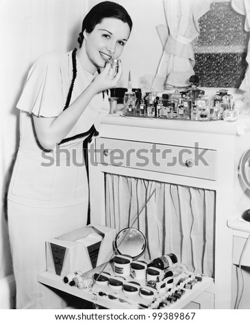 Young woman at her vanity applying lipstick