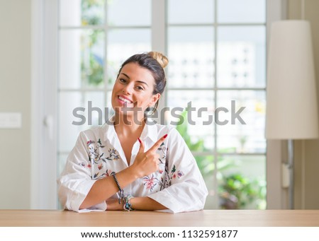 Young woman at home cheerful with a smile of face pointing with hand and finger up to the side with happy and natural expression on face looking at the camera.