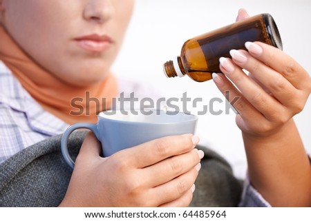 Young woman at home having flu, feeling bad, taking medicine, vitamin, drinking hot tea in bed.?