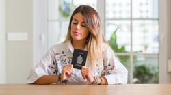 Young woman at home holding a passport of Canada with a confident expression on smart face thinking serious