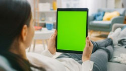 Young Woman at Home Resting on a Couch Using with Green Mock-up Screen Tablet Computer in Vertical Portrait Mode. Woman Using Tablet Device, Browsing Internet, Watching Content, Videos.
