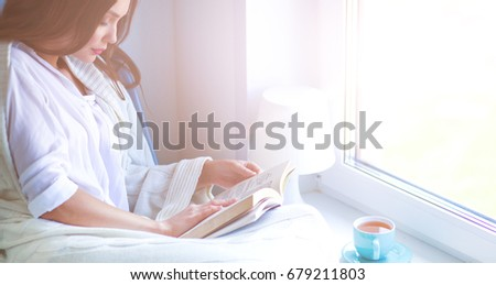 Young woman at home sitting near window relaxing in her living room reading book and drinking coffee or tea #679211803