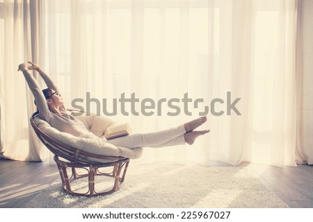Young woman at home sitting on modern chair in front of window relaxing in her living room reading book, instagram toning